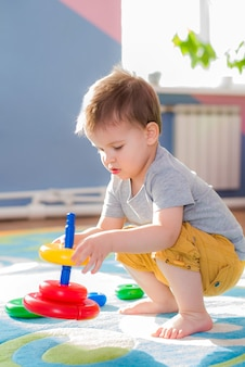 Маленький ребенок собирает пираимду, сидя на полу