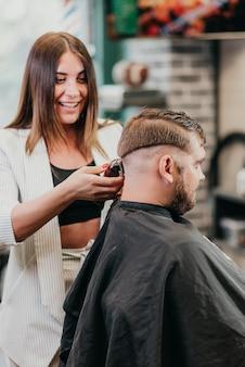 Красивая девушка-парикмахер режет бородатого мужчину в салоне