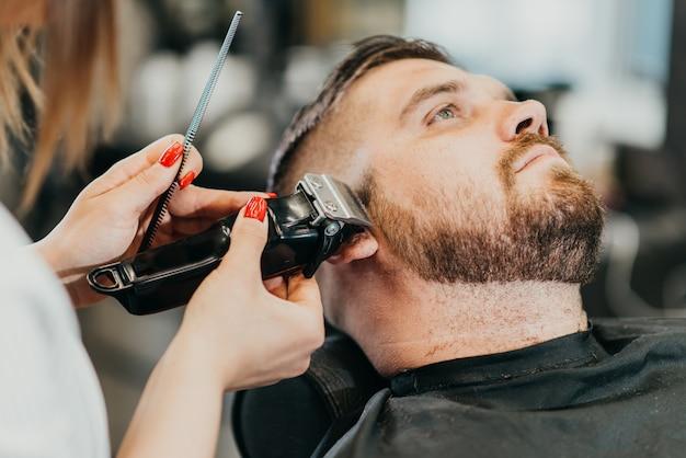 Парикмахер стрижет бороду брутальному мужчине в салоне