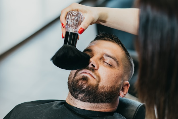 Девушка-парикмахер удаляет остатки волос щеткой после стрижки