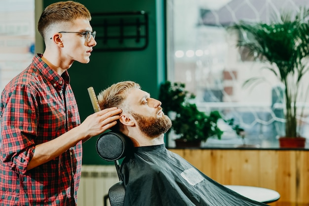 理髪師はサロンで男にひげを切る