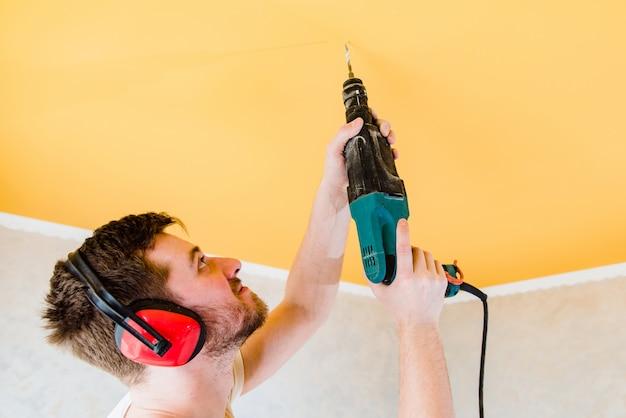 Работник делает ремонт и сверла в потолке