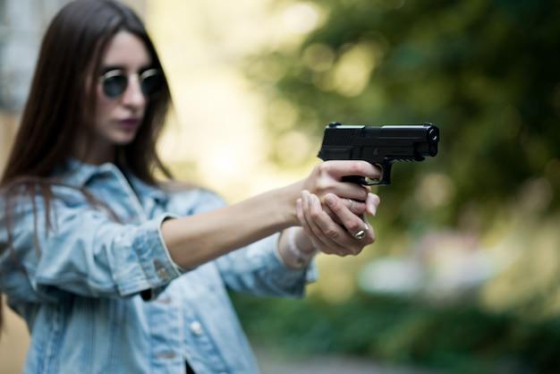 路上で銃を持つ少女が撮影することを学ぶ