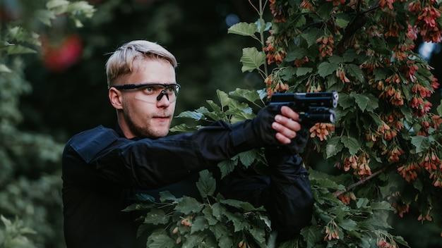 Инструктор с пистолетом в лесу ведет цель и позирует
