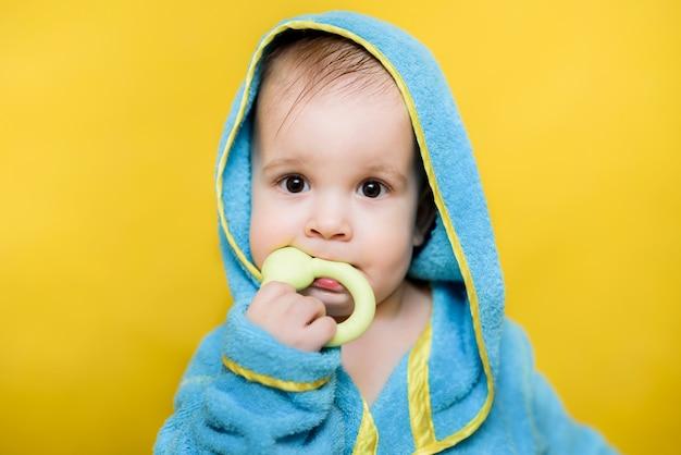 お風呂の後の赤ちゃんが座っておもちゃをかむ