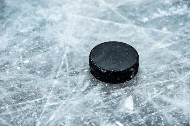 Хоккейная шайба лежит на снегу крупным планом
