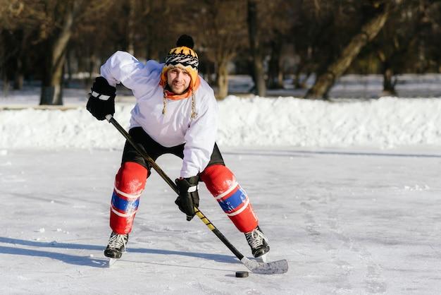 Мужчина играет в хоккей на катке