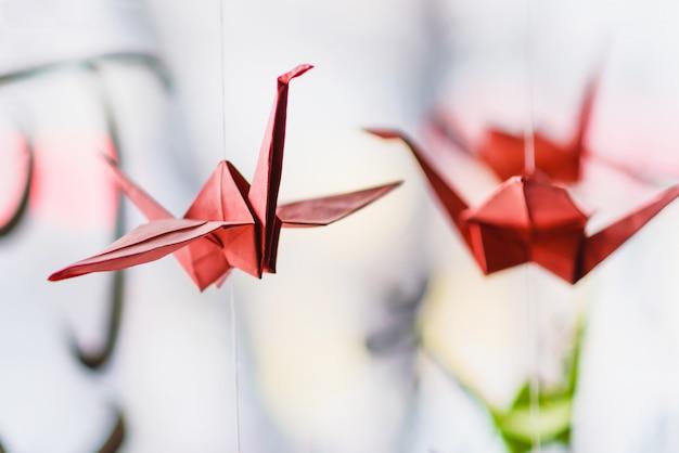 Оригами висит на фоне иероглифов