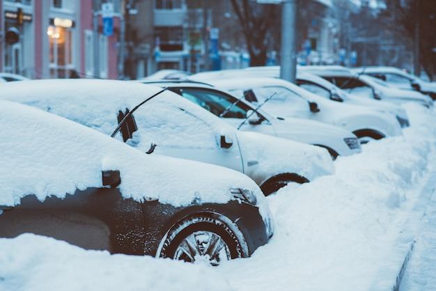 車は雪に覆われた道路に沿って駐車されています