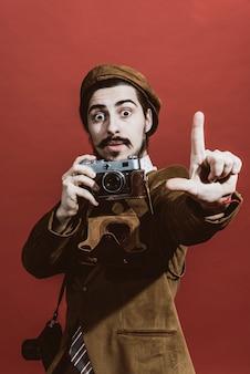 フィルムカメラでスタジオでポーズをとる非常に肯定的な写真家