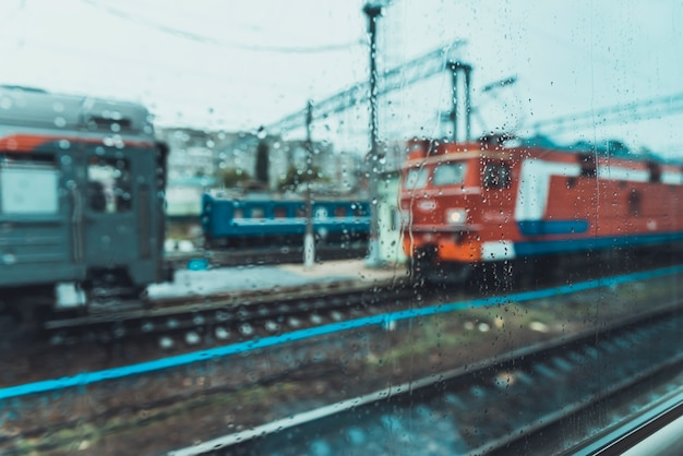 雨天の電車の窓からの眺め。