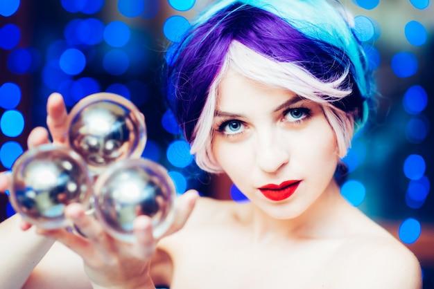 美しい少女は透明なボールでジャグリングを示します