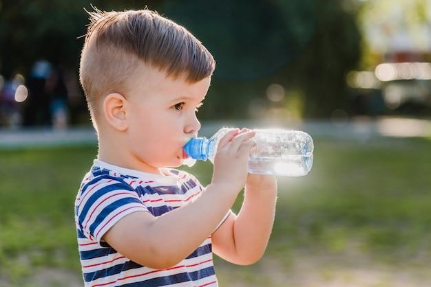 ハンサムな男の子は外の晴れた日にボトルからきれいな水を飲む