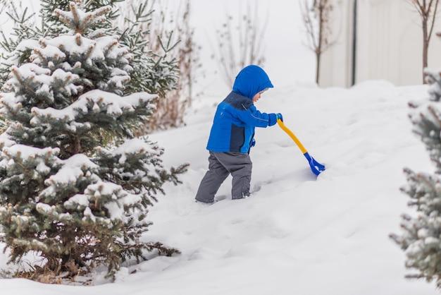 Маленький мальчик копает снег лопатой зимой.