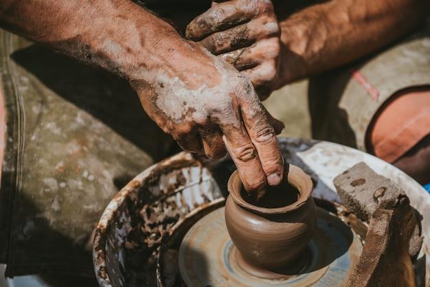 Мастер делает горшок с глиной