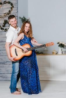 ギターを弾く彼女の夫の楽しみと美しい若い妊娠中の女性。