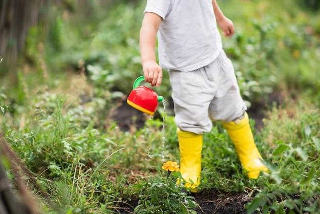 Ребенок в саду поливает цветы лейкой.