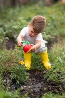 水まき缶で花に水をまく庭の子供。