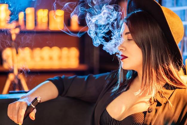 ヴェイピング。クラブで電子タバコを吸って美しい少女。
