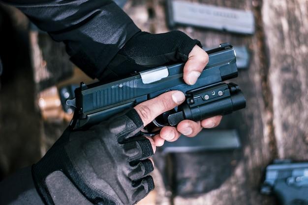 スポーツ射撃インストラクターが武器のクローズアップをチェック