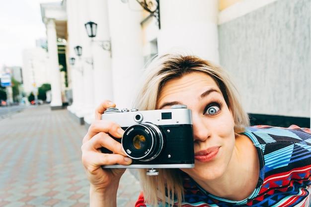 女性が街でレトロなカメラを撮影