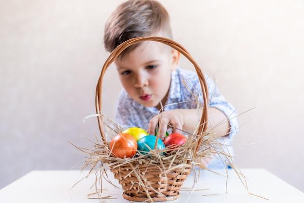 小さな男の子は、白い背景の上のテーブルからバスケットからイースターエッグを取ります。