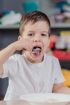 子供はオートミールのおで朝食をとります。少年は自宅の台所のテーブルに座って食事をします。