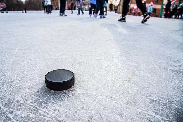ブラックホッケーパックはスタジアムで氷の上にあります。