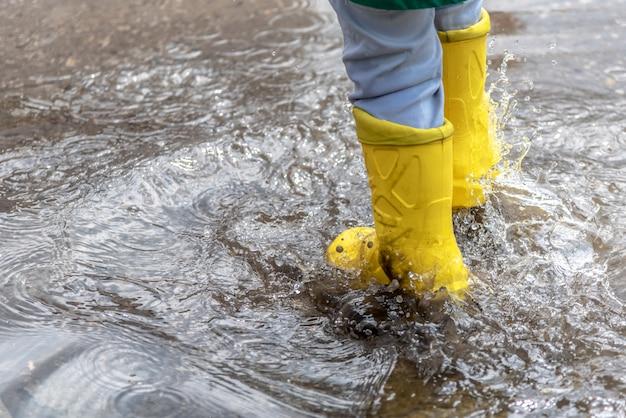 Маленький мальчик прыгает в луже в резиновых сапогах в дождливую погоду
