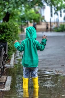 Маленький мальчик стоит в луже в резиновых сапогах в дождливую погоду