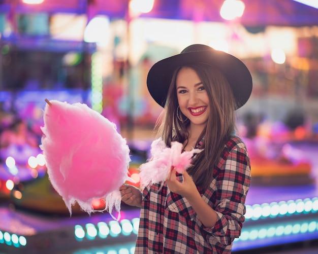 Красота девушка с ватой конфеты в справедливой со многими огнями
