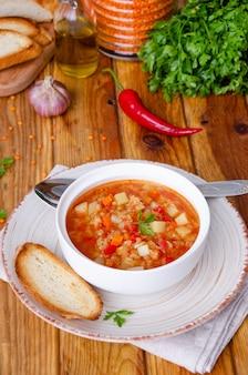 Острый суп с красной чечевицей, помидорами, луком-пореем, болгарским перцем, морковью и картофелем.
