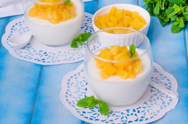 Баварский крем-мусс с ванилью и персиками в сиропе в стакане