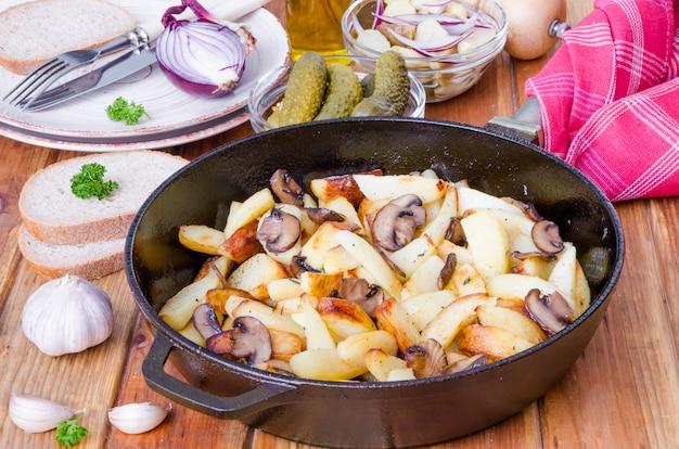 木製の背景に鍋にキノコとフライドポテト