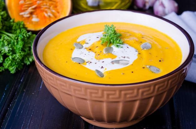 赤レンズ豆と木製のボウルにニンジンとカボチャのクリームスープ。