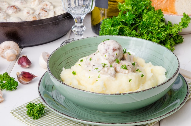 Фрикадельки в сливочном соусе с грибами и картофельным пюре в тарелке