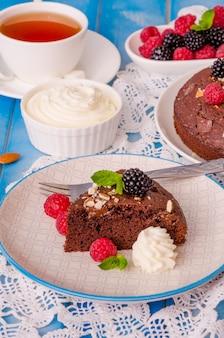 ラズベリー、ブラックベリー、アーモンド、木製の背景にホイップクリームとチョコレートケーキブラウニー。
