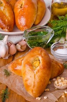 Традиционные русские и украинские дрожжевые мини-пирожки с горошком и чесночным соусом. деревенский стиль