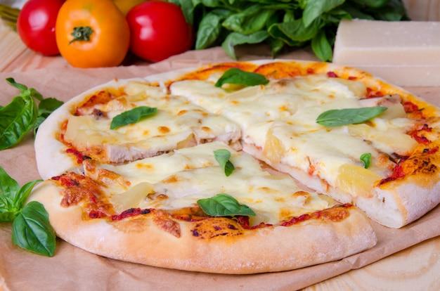 イタリアのピザ、トマトソース、ハム、パイナップル、チーズ、木製の表面に新鮮なバジル