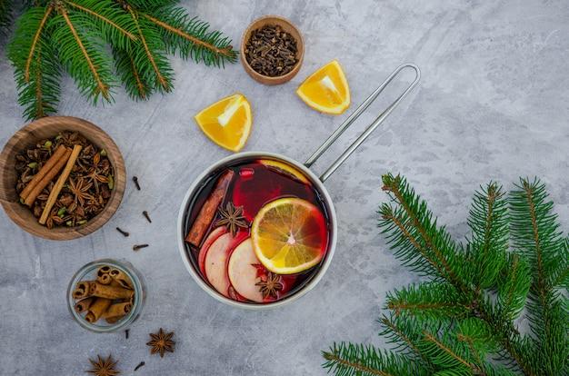 グレーの表面に鍋にリンゴ、オレンジ、ジンジャー、シナモン、カルダモン、スターアニスと自家製ホットワイン