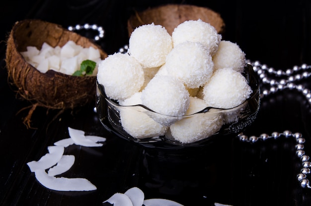 アーモンドと木製の表面にクリームチーズのおいしい自家製ココナッツキャンディー