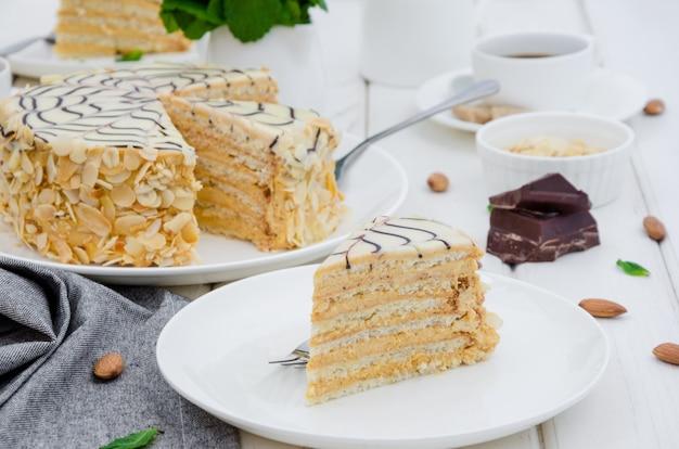 コーヒー、ミント、アーモンドのカップと石のテーブルの上の白い皿に伝統的なハンガリーエステルハージケーキ。