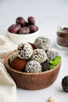 Энергетические шары. трюфели из фиников, грецких орехов, фундука и какао в деревянной миске на светлом фоне. здоровый десерт, без сахара, без глютена.