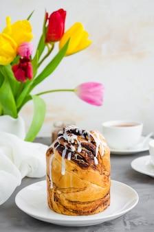 Пасхальный фон. пасхальный кулич с шоколадной ореховой кремовой и сахарной глазурью сверху на белой тарелке на бетонном фоне. вертикальная ориентация.