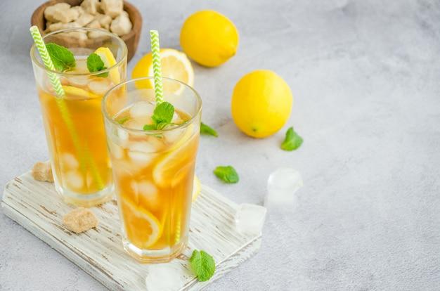 Ледяной чай с лимоном, коричневый сахар, листья мяты и кубики льда в стакане на доске на светлом фоне. летний освежающий напиток.