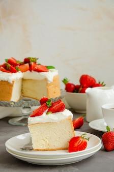 Ангел еда торт со взбитыми сливками и кусочками свежей клубники на вершине на бетонном фоне.