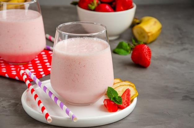 イチゴのスムージーやコンクリートの灰色の背景にあるガラスのバナナとミルクセーキ。夏の冷たい飲み物。