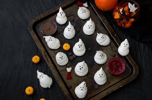 黒い背景に古い天板にチョコレートとベリーのソースでハロウィンメレンゲを幽霊します。ハロウィーンパーティーのための食品のアイデア。