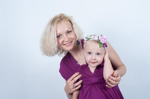 白い表面のスタジオで金髪のママと娘
