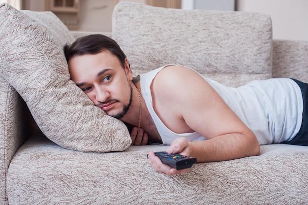 男はソファで面白い映画を見ています